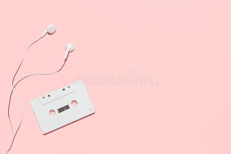Белые кассета и наушники на розовой предпосылке стоковое фото