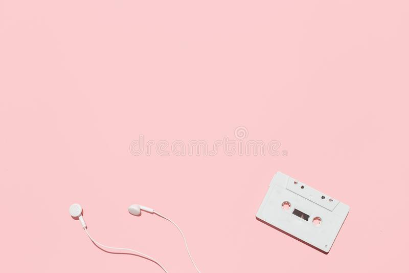 Белые кассета и наушники на розовой предпосылке стоковые фотографии rf