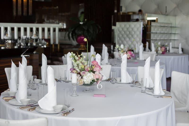 Белые салфетки стоят в белых плитах и букете свежих цветков в центре, который служат таблицы в ресторане Очистите белизну стоковая фотография rf