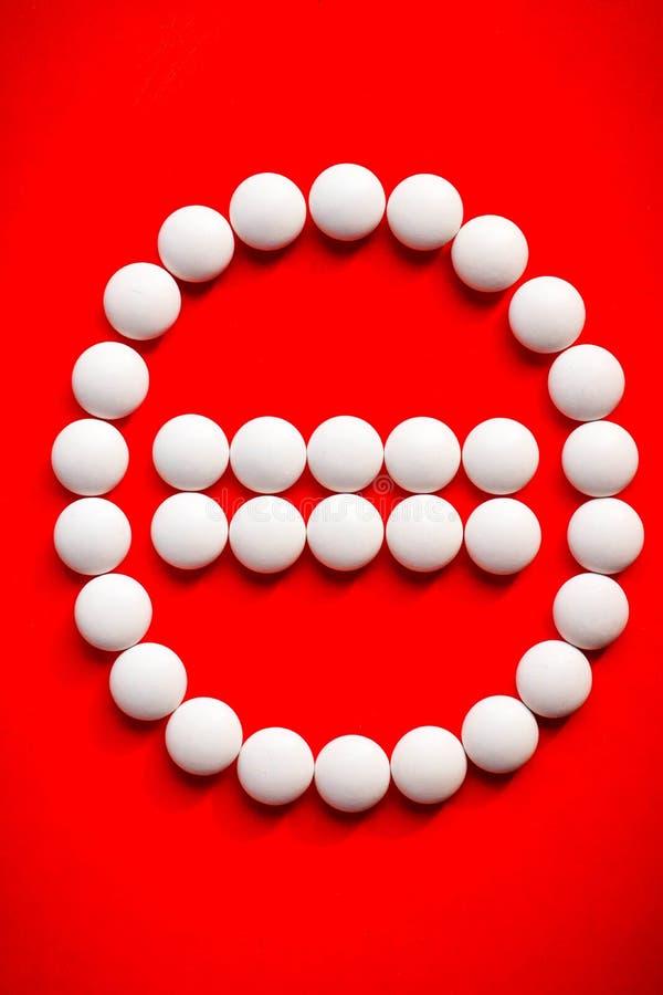 Белые таблетки аранжируют в знаке стопа Красная предпосылка стетоскоп дег микстуры лож принципиальной схемы установленный стоковые изображения rf