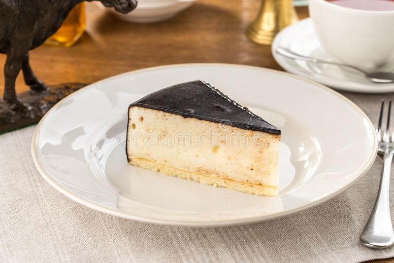 Белый торт суфла с темной замороженностью на деревянном столе стоковое фото