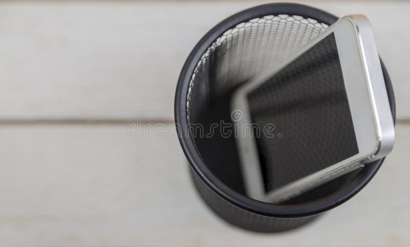 Белый сотовый телефон в мусорном баке на запачканной предпосылке, электронной ненужной концепции стоковые изображения rf