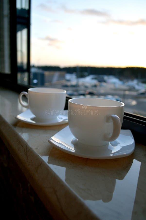 2 белых чашки кофе на windowsill стоковое фото