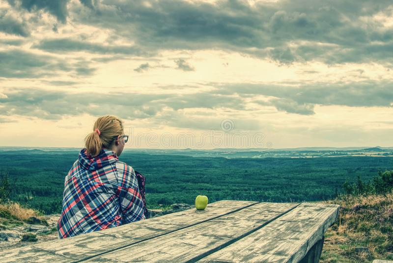 Белокурая девушка сидит самостоятельно на крае над хлябью стоковая фотография