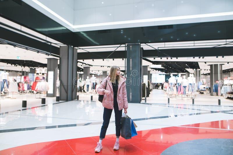 Белокурая девушка с хозяйственными сумками в ее руках стоит в торговом центре на фоне магазина одежды стоковое изображение