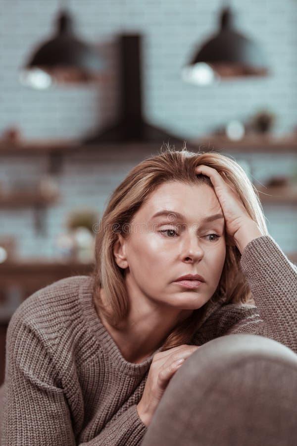 Белокур-с волосами коммерсантка сидя в кухне дома стоковое изображение