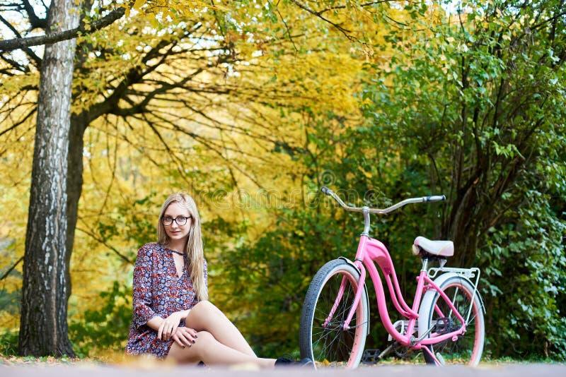 Белокурое модное длинн-с волосами привлекательное платье девушки вкратце с велосипедом дамы в солнечном парке стоковая фотография