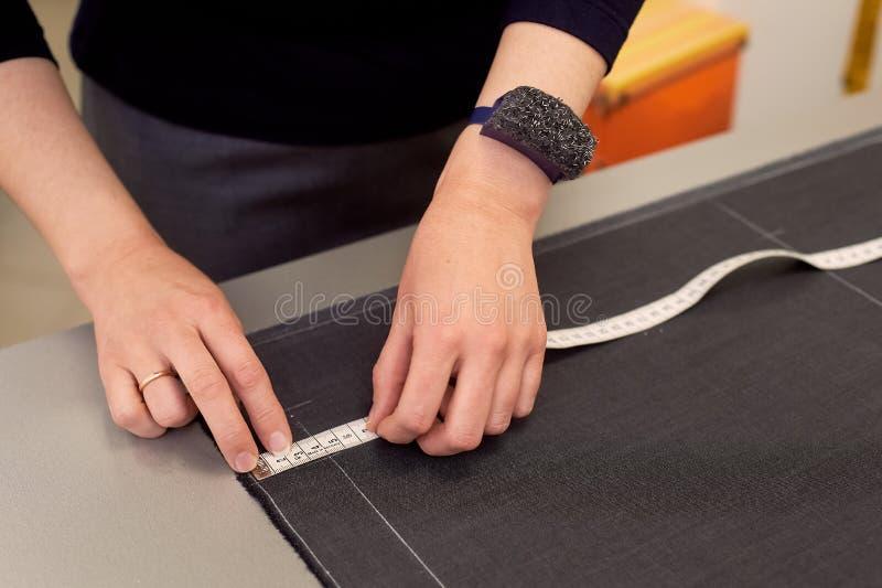 Белошвейка кладет вне ткань для резать используя дюймы Руки в съемке стоковые фото