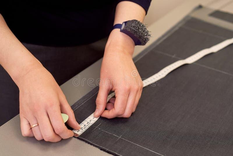 Белошвейка кладет вне ткань для резать используя дюймы Руки в съемке стоковые изображения