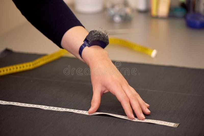 Белошвейка кладет вне ткань для резать используя дюймы Руки в съемке стоковое фото