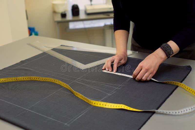 Белошвейка кладет вне ткань для резать используя дюймы Руки в съемке стоковое фото rf