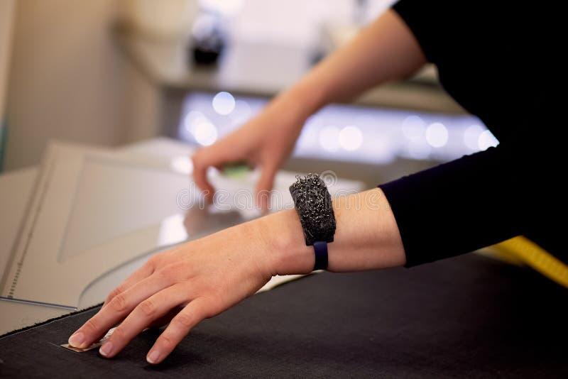Белошвейка кладет вне ткань для резать используя дюймы Руки в съемке стоковое изображение