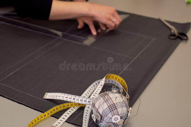 Белошвейка кладет вне ткань для резать используя дюймы Руки в съемке стоковое изображение rf