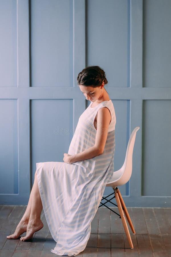 Беременная женщина внутри комнаты нежно штрихует живот стоковое фото