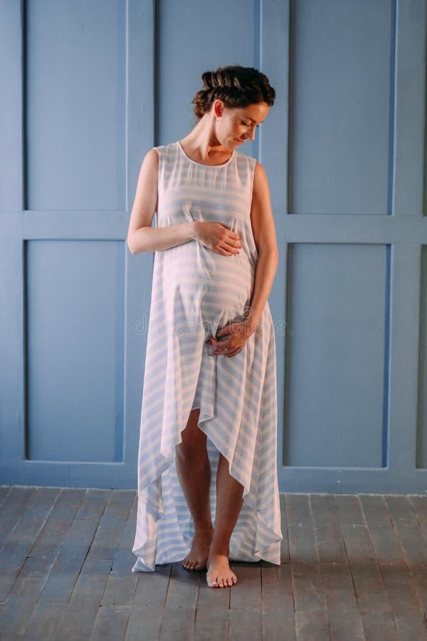 Беременная женщина внутри комнаты нежно штрихует живот стоковые изображения rf
