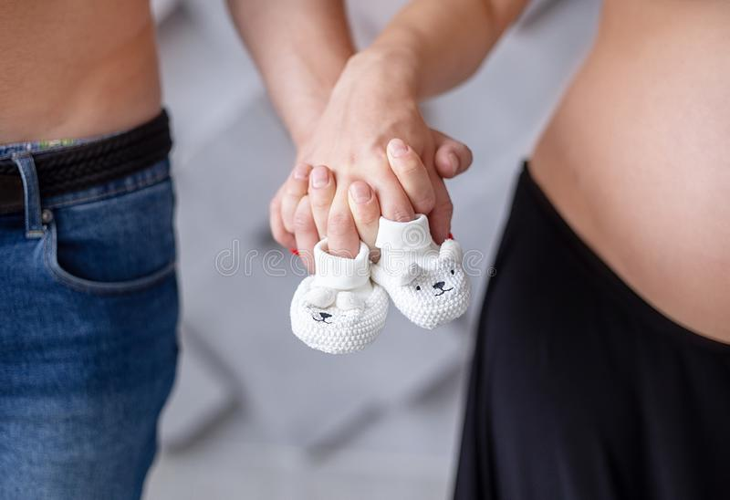 Беременная женщина и ее супруг держа их руки ее беременная женщина супруга стоковые изображения rf