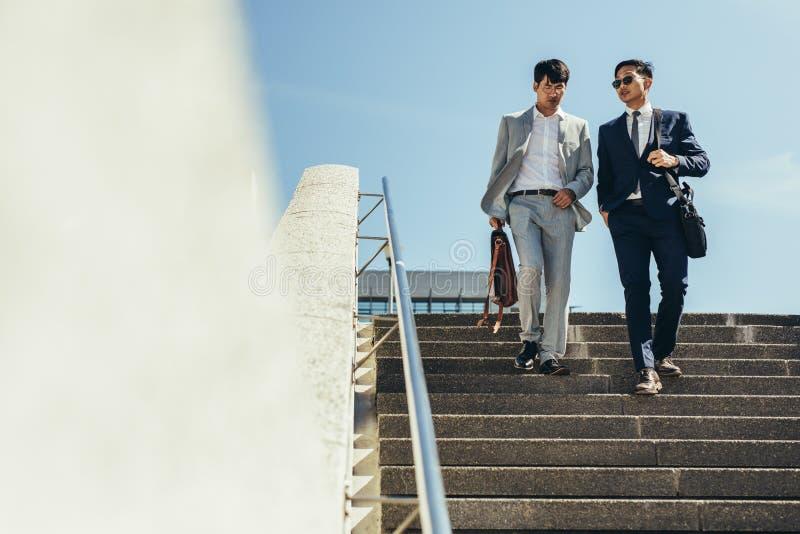 Бизнесмены говоря и идя вниз с шагов стоковое изображение rf