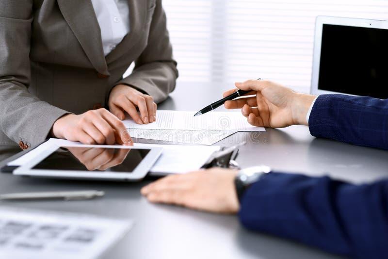 Бизнесмены и юрист обсуждая бумаги сидя на таблице, конец-вверх контракта рук Деятельность сыгранности или группы стоковое фото