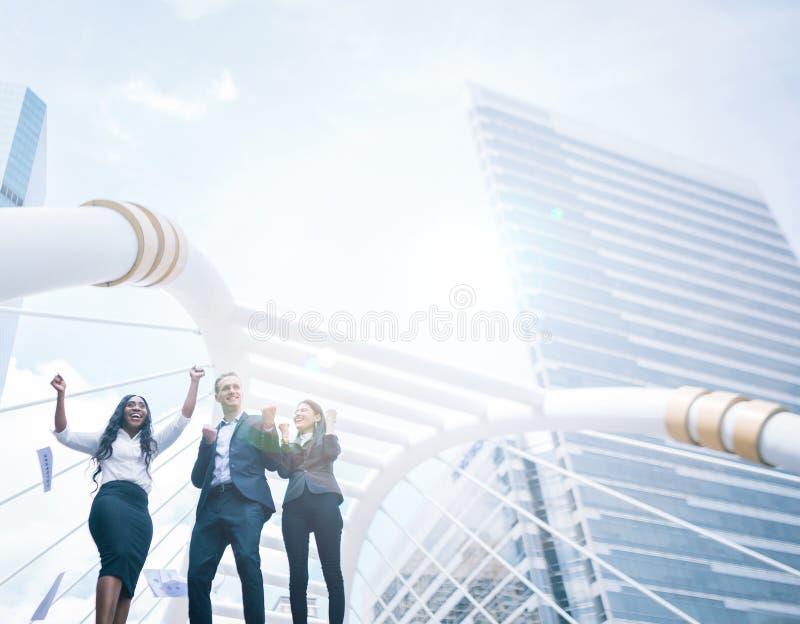 Бизнесмены празднуя путем бросать бумаги в воздухе во взгляде здания города стоковые фотографии rf