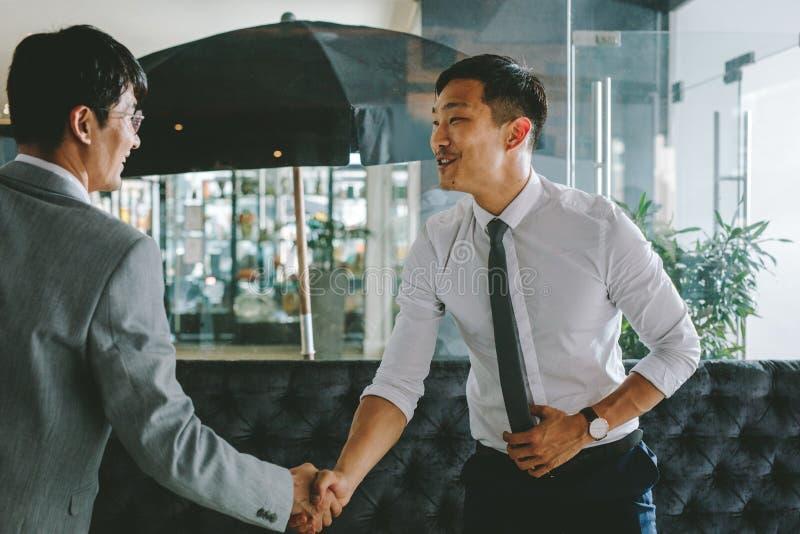 Бизнесмены приветствуя один другого с рукопожатием стоковая фотография