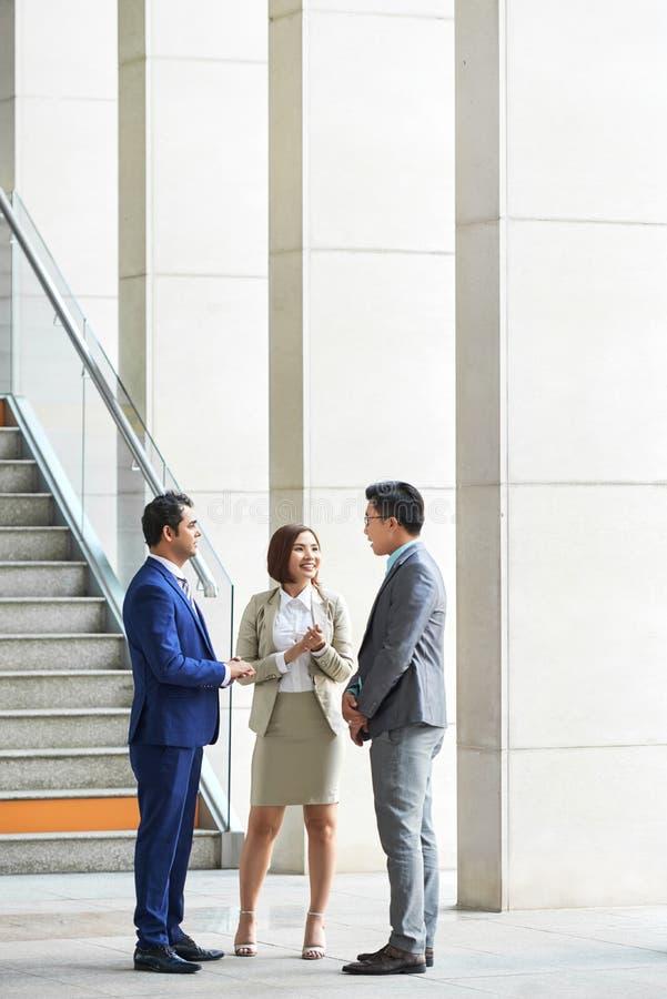 Бизнесмены стоя на коридоре офиса стоковое изображение rf