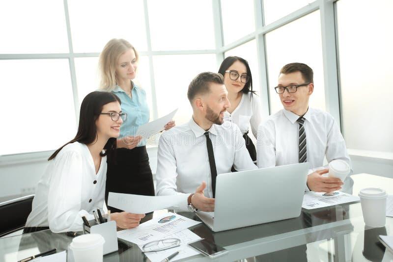 Бизнесмены работая и связывая пока сидящ на столе офиса стоковые изображения
