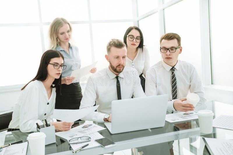 Бизнесмены работая и связывая пока сидящ на столе офиса стоковая фотография rf
