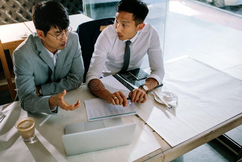 Бизнесмены обсуждая новый проект в кофейне стоковое фото
