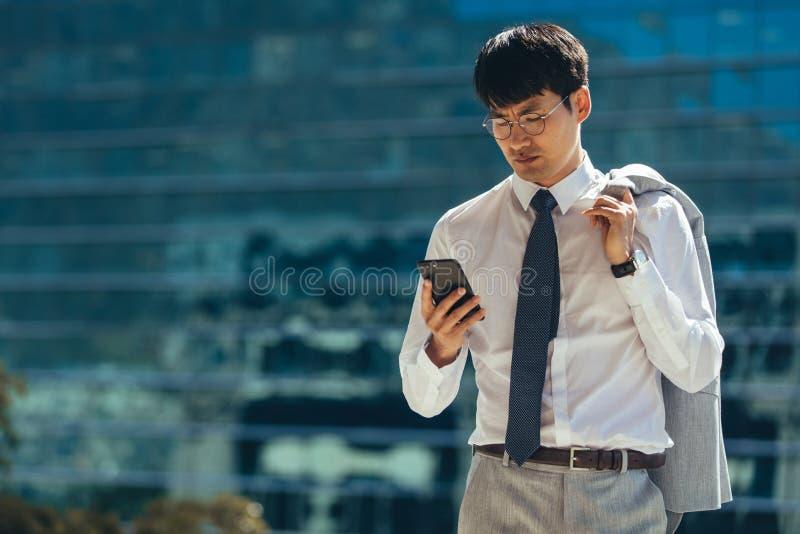 Бизнесмен идя outdoors используя его умный телефон стоковые изображения