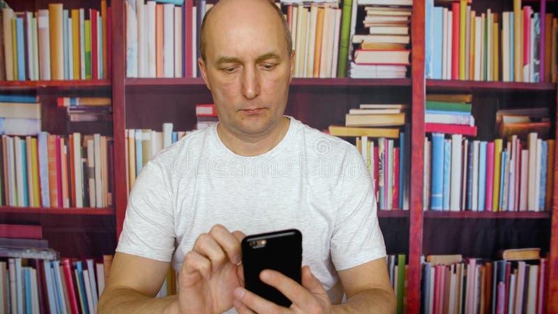 Бизнесмен используя мобильный телефон в домашнем офисе на предпосылке bookcase стоковая фотография rf