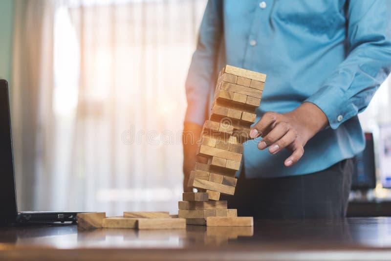 Бизнесмен комплектуя деревянные руки башни опасности терпеть неудачу блока держа игру проблемы стоковые изображения