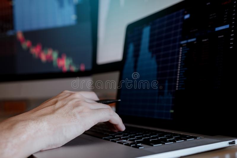 Бизнесмен печатая на ноутбуке клавиатуры и работая торгуя фондовой бирже в комнате офиса стоковые изображения rf