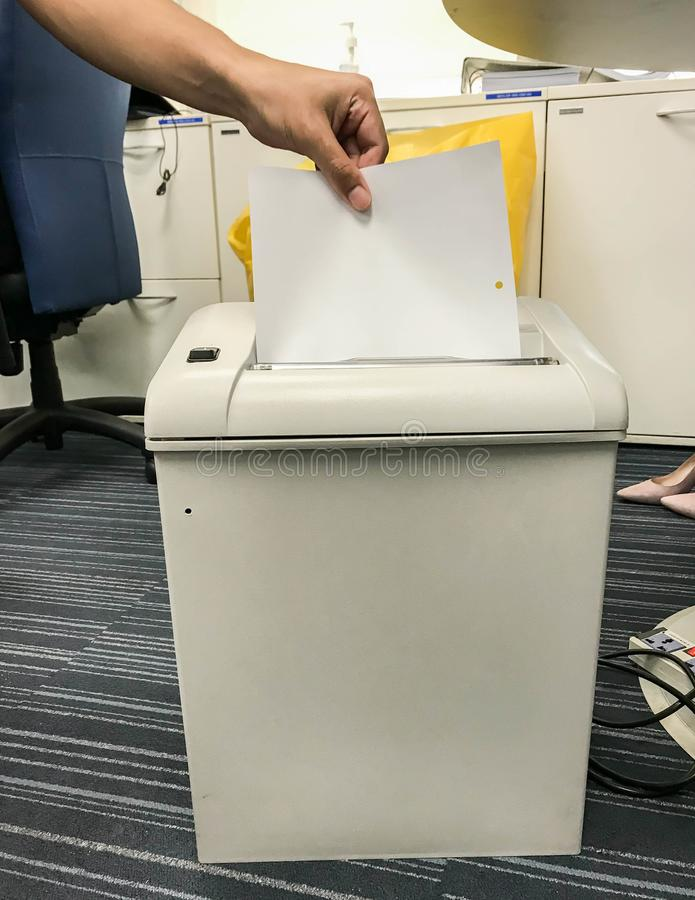 Бизнесмен положил конфиденциальную информацию и документы в старую бумажную shredding машину в офисе стоковые фотографии rf