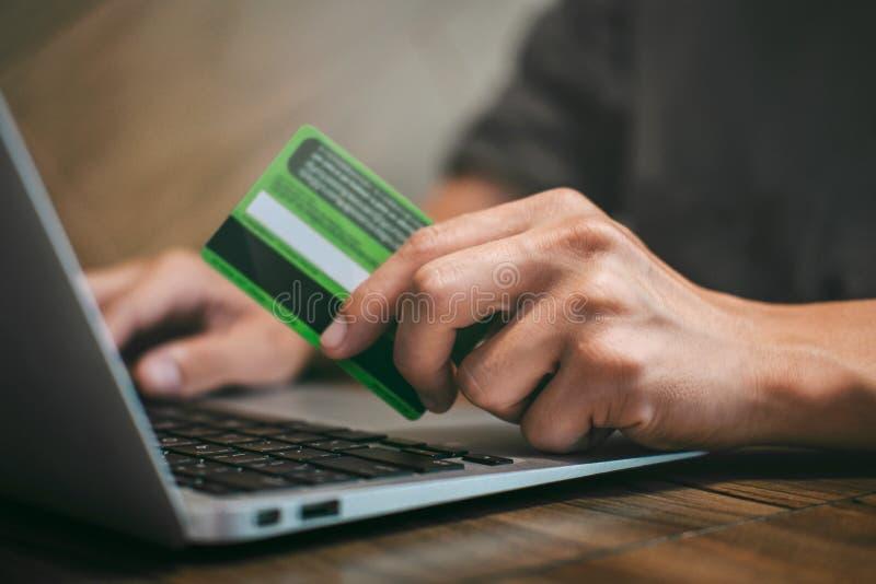 Бизнесмен держа кредитную карточку и печатая на ноутбуке для онлайн покупок и оплаты делает приобретение в Интернете, онлайн стоковые фотографии rf