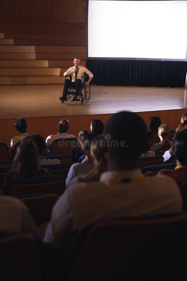 Бизнесмен сидя на кресло-коляске и давая представление к аудитории стоковое фото rf