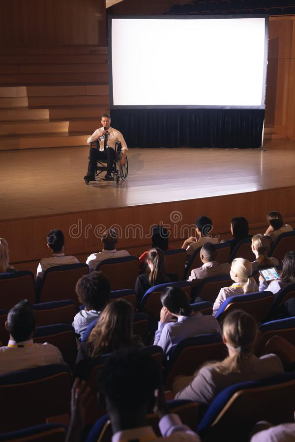 Бизнесмен сидя на кресло-коляске и давая представление к аудитории стоковое изображение rf