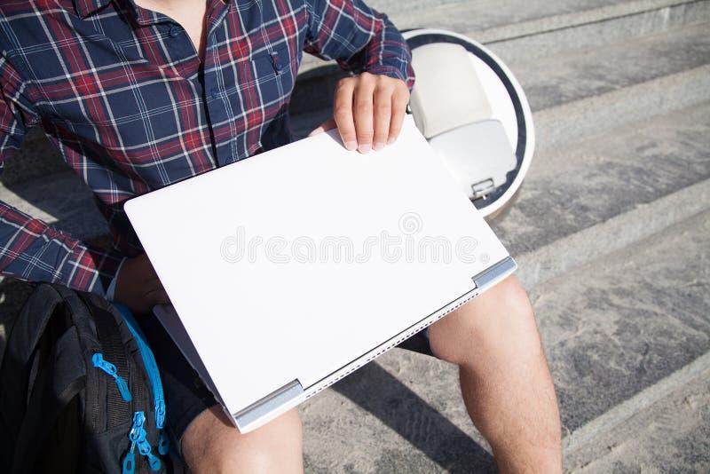 Бизнесмен сидя на улице раскрывает его ноутбук стоковые фотографии rf