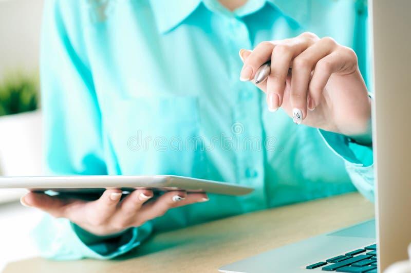 Бизнес-леди смотря и изучая статистику на крупном плане дисплея планшета Женская левая рука держит ручку, право держит планшет стоковая фотография