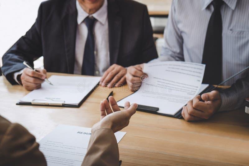 Бизнес-леди объясняя об его профиле менеджеру 2 отборочных комитетов сидя внутри во время собеседования для приема на работу, инт стоковая фотография rf