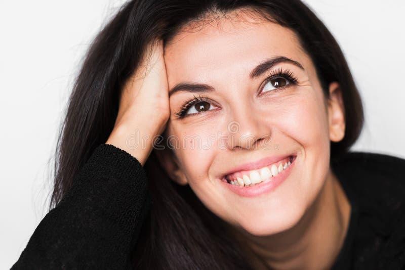 Близкий поднимающий вверх портрет женщины брюнета жизнерадостной со здоровой зубастой улыбкой с рукой на волосах стоковое изображение