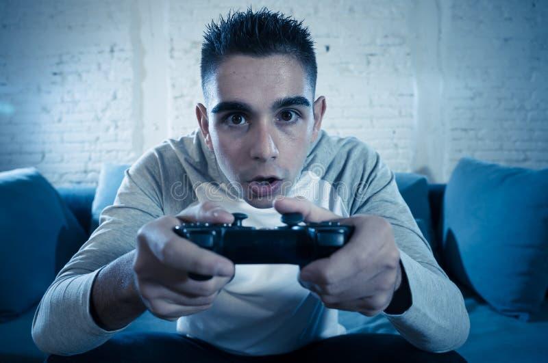 Близкий поднимающий вверх портрет молодого пристрастившийся человека играя видеоигру вечером в концепции игры и наркомании стоковое изображение rf