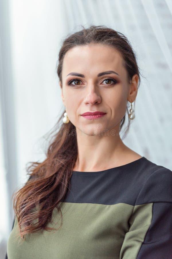 Близкий портрет серьезного милого брюнета в платье дела с предпосылкой белых прозрачных занавесов Тюль стоковое изображение rf