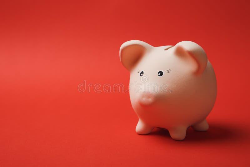 Близкое поднимающее вверх фото розового piggy банка денег на яркой красной предпосылке стены Накопление денег, вклад, банк стоковые фото