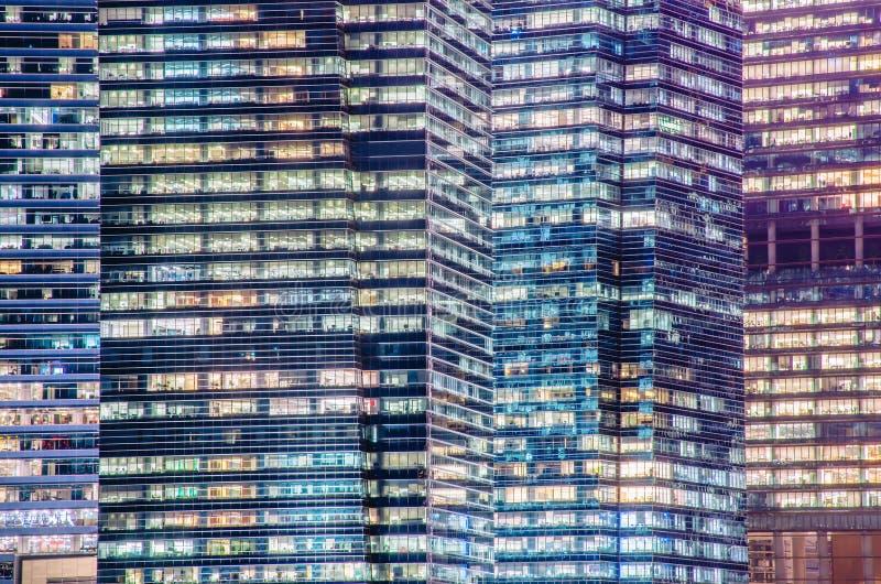 Близко - вверх высок-детальной картины окон ночи современной метрополии стоковая фотография