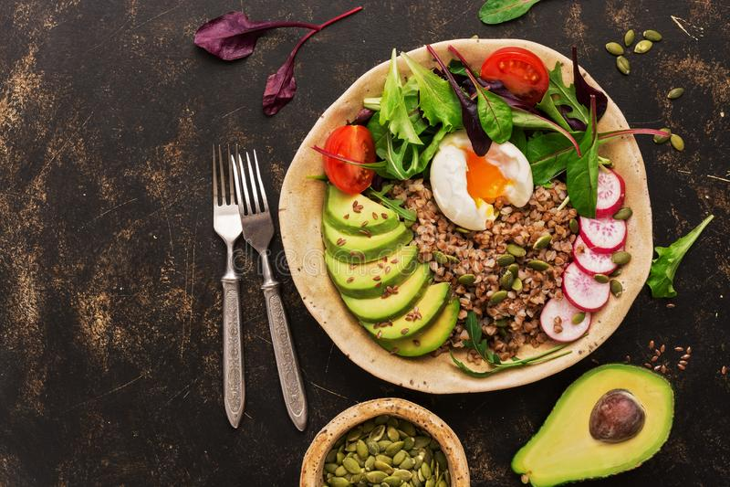 Блюдо шара Будды с кашой гречихи, салатом свежего овоща с авокадоом, редиской, листьями мангольда, arugula, томатом и семенами, стоковое фото rf