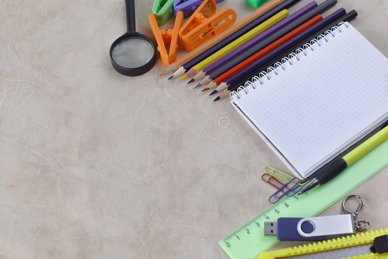 Блокнот для принимать примечания и школьные принадлежности на бумажной предпосылке Фото с космосом экземпляра стоковое фото
