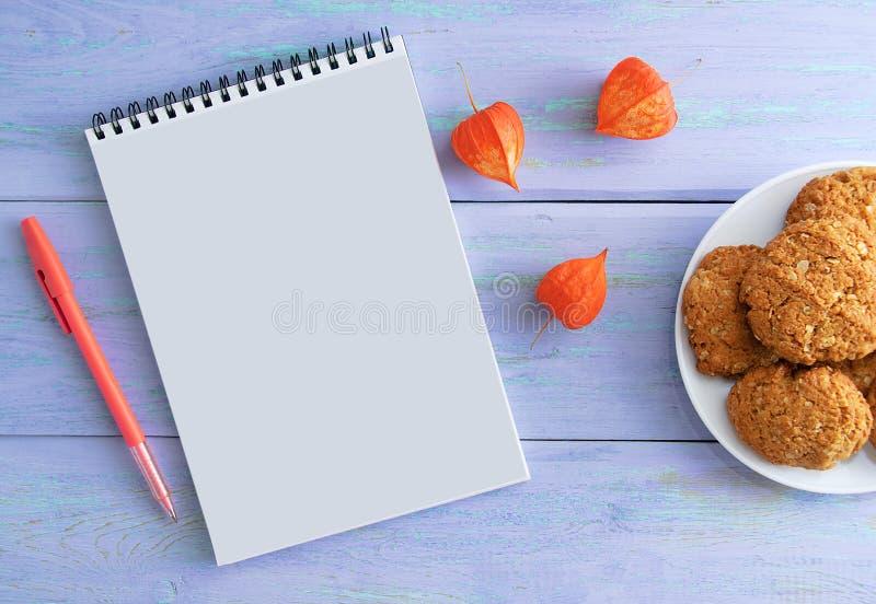 Блокнот, ручка, высушенные цветки и печенья плита На деревянной голубой предпосылке стоковые изображения rf