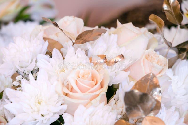 букет звенит венчание Букет свадьбы белых и золотых роз Свадьба в золотых цветах стоковое фото