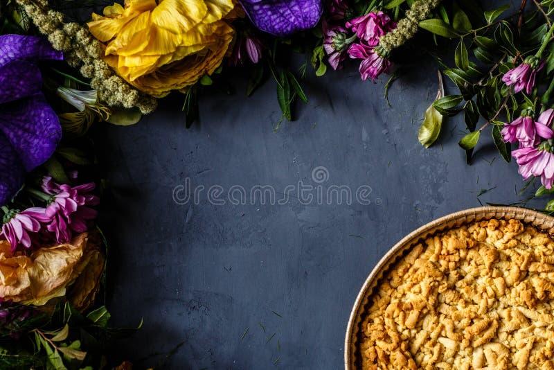 Букет ярких цветков и яблочного пирога лежа на серой предпосылке Плоское положение Взгляд сверху установьте текст стоковая фотография rf