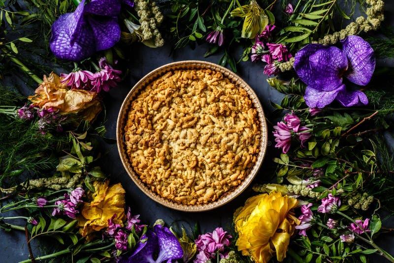 Букет ярких цветков и яблочного пирога лежа на серой предпосылке Плоское положение Взгляд сверху стоковое фото rf
